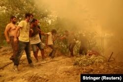 Egy tömlőt tartó férfit segítenek fel társai a tűzvésztől pusztított Guvesz faluban, Évia szigetén 2021. augusztus 8-án