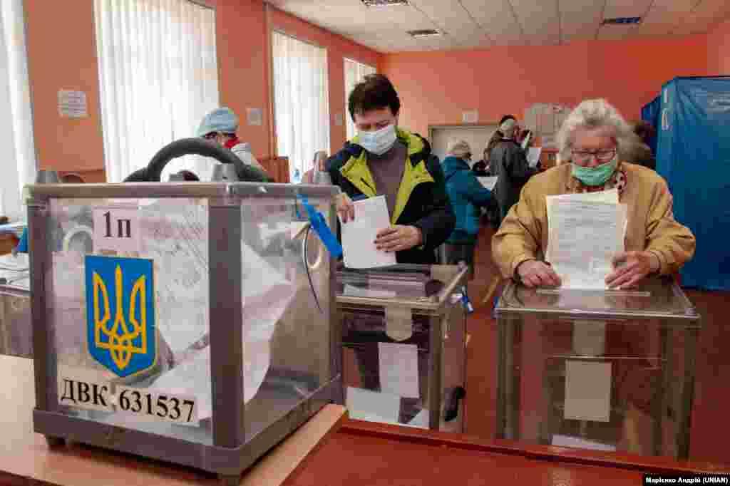 Виборці кидають бюлетені в урну для голосування на дільниці у Харкові