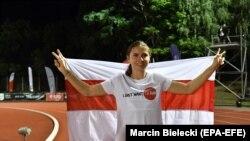 Kriszcina Cimanouszkaja a belarusz ellenzék zászlajával egy futóversenyen a lengyelországi Szczecinben 2021. augusztus 15-én