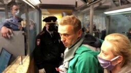 Russian police speak with Aleksei Navalny (with his wife, Yulia, right) before leading him away at Sheremetyevo airport in Moscow on January 17.