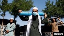 Një qytetar afgan pret para një fabrike në Kabul për të mbushur cilindrin me oksigjen.