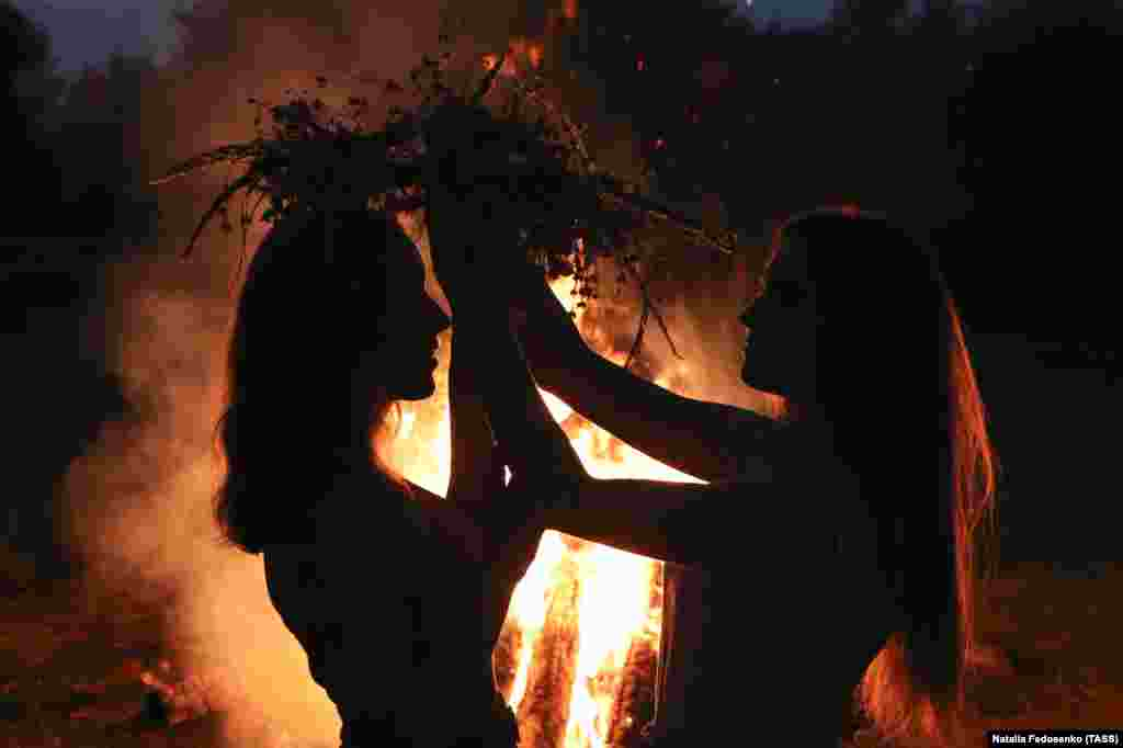 Girls put on flower wreaths by a bonfire during Ivana-Kupala celebrations held by the Pripyat River in the town of Turau in Belarus's Homel region on July 6.