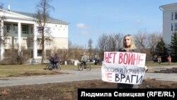 """Орусиялык пикетчи """"Согушка жол жок! Орусия менен Украина кас душмандар эмес"""" деген сөздөрү бар жарнакты көтөрүп турат. Псков шаары, Орусия. 2021-жылдын 11-апрели."""