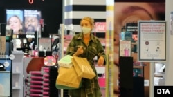 Жена пазарува в мол в последния ден преди да влязат в сила новите ограничения, сред които е и забрана за работа на големите търговски центрове.