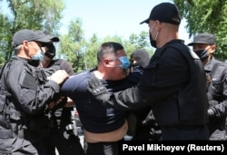 A man wearing a protective face mask is detained during an unsanctioned rally held by Kazakh opposition supporters in Almaty in June 2020.