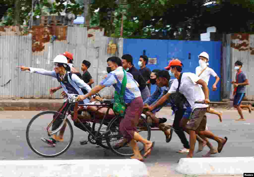 People transport a person who was shot during a security force crackdown on anti-coup protesters in Thingangyun, Yangon, Myanmar March 14, 2021. Picture taken on March 14, 2021.