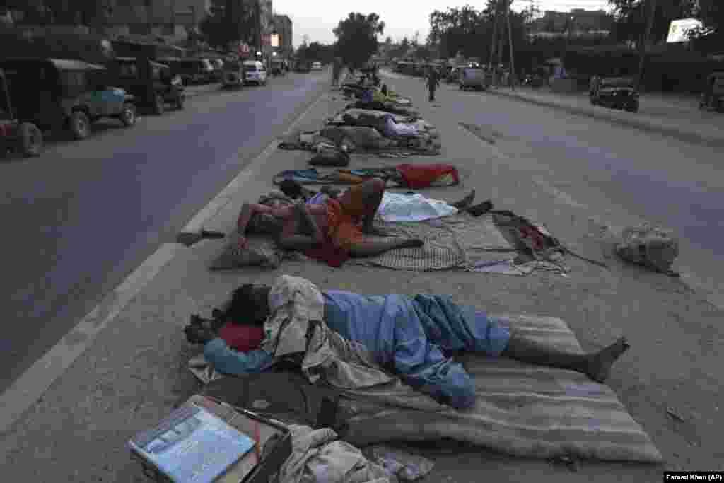 Рабочие спят под открытым небом жарким летним утром в Карачи, Пакистан