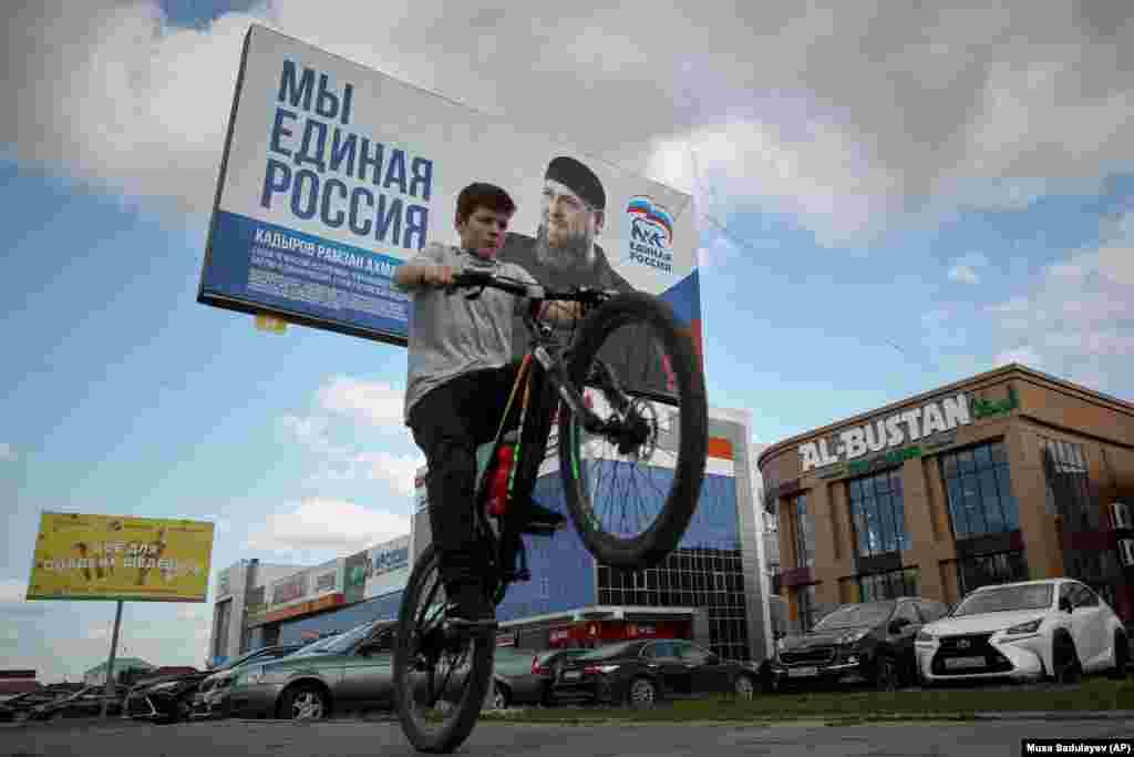 Хлопчык праяжджае на ровары ля перадвыбарнага плякату кіруючай расейскай партыі «Адзіная Расея» з партрэтам чачэнскага лідэра Рамзана Кадырава.