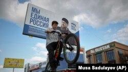 Хлопчык праяжджае на ровары ля перадвыбарнага пляката кіроўнай расейскай партыі «Единая Россия» з партрэтам чачэнскага лідэра Рамзана Кадырава