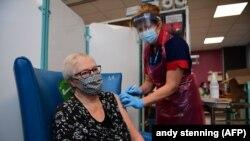 Nagy-Britanniában elkezdődött a szigetország történetének legnagyobb oltási programja. A képen egy ápoló beadja a Pfizer-BioNTech COVID-19 vakcinát Trixie Walker páciensnek egy sheffieldi kórházban, Yorkshire-ben, 2020. december 8-án.