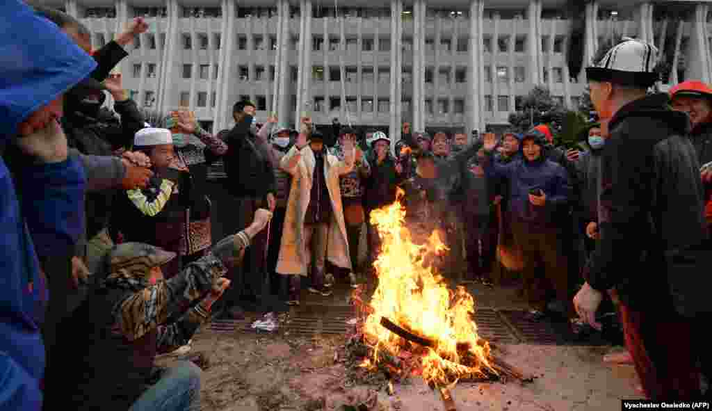 People protesting the results of the parliamentary vote gather by a bonfire in front of the seized White House in Bishkek.