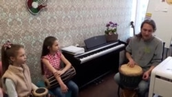 Музыка і выкладчык Арцём Фрэнкель пры дапамозе барабанаў «прышчапляе» адчуваньне рытму юным вакалісткам