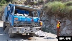 Pakistani rescue officials inspect the scene of a blast that targeted a bus carrying Chinese engineers to the site of the Dasu Dam in Upper Kohistan on July 14.