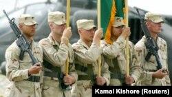 Солдаты США держат американский и афганский флаги во время церемонии передачи командования на авиабазе Баграм к северу от Кабула. 27 мая 2003 года