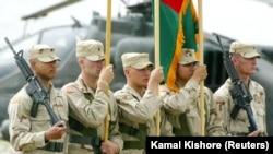 Кабулдан солтүстікке қарай орналасқан Баграм әскери әуе базасында өткен шара кезінде АҚШ пен Ауғанстан туларын ұстап тұрған америкалық сарбаздар. 27 мамыр 2003 ж.