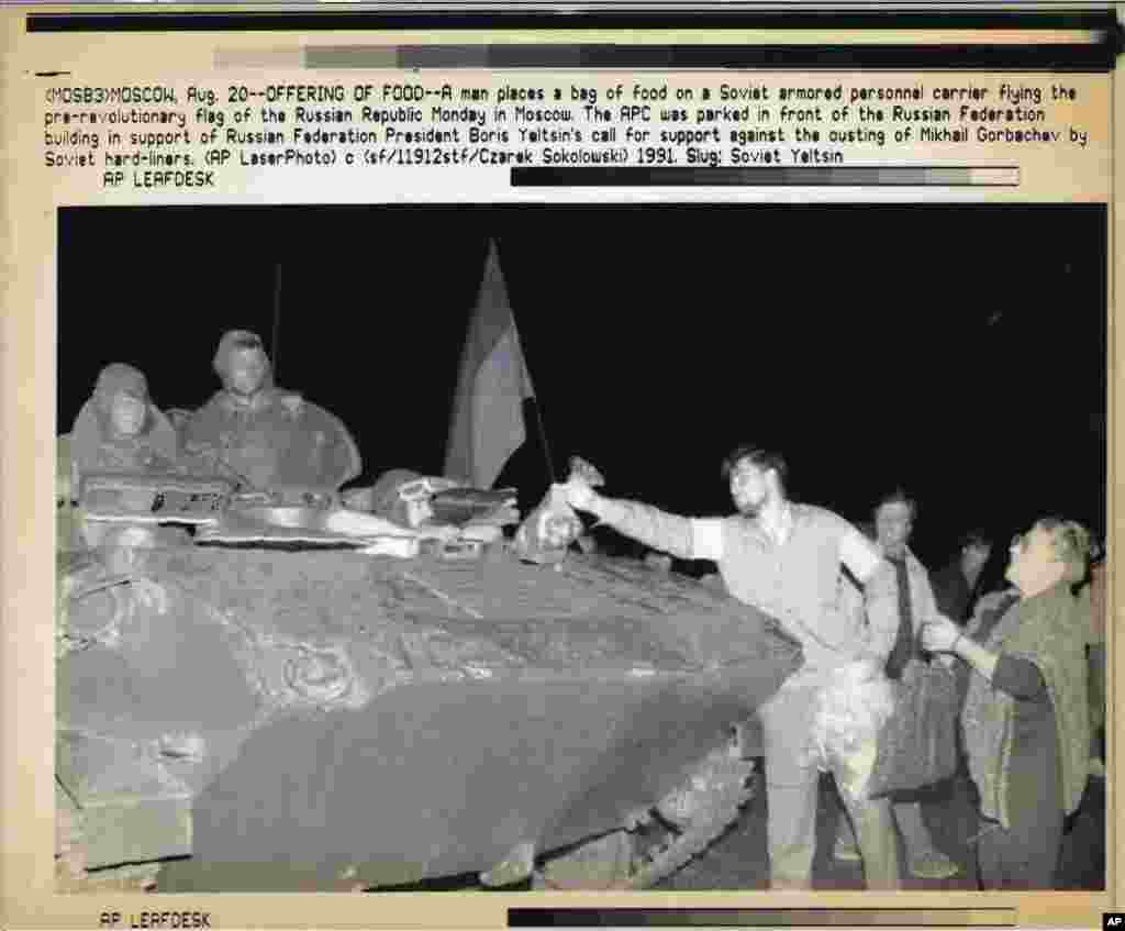 Demonstrators offer food to Soviet soldiers who broke away from their unit to support the anti-coup leaders.