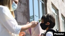 Armenia -- A teacher measures a first grader's temperature at the entrance to a school in Yerevan, September 14, 2020.