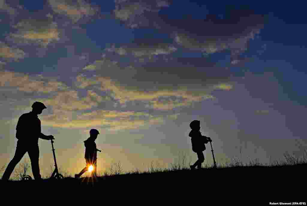 A father and his sons walk at sunset near a dam in Bucharest. (epa-EFE/Robert Ghement)