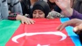 A woman cries at the coffin of an Azerbaijani soldier killed in fighting over the breakaway Nagorno-Karabakh region at a funeral ceremony in the Beylagan district on September 30.
