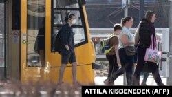 Utasok, egyikük maszkban Budapesten 2020. március 19 -én
