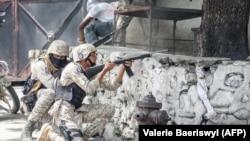Бойцы гаитянских сил безопасности ведут перестрелку с вооруженными людьми, подозреваемыми в убийстве Жовенеля Моиза, рядом с полицейским участком в Порт-о-Пренсе. 8 июля 2021 года