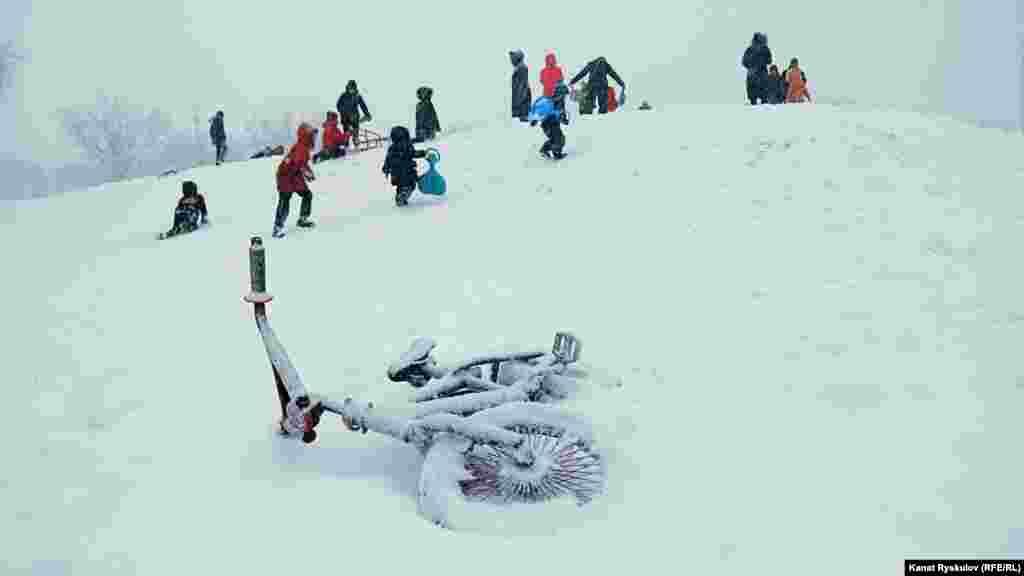 """Чей-то велоспед остался под толстым слоем снега, зима пришла """"внезапно""""."""