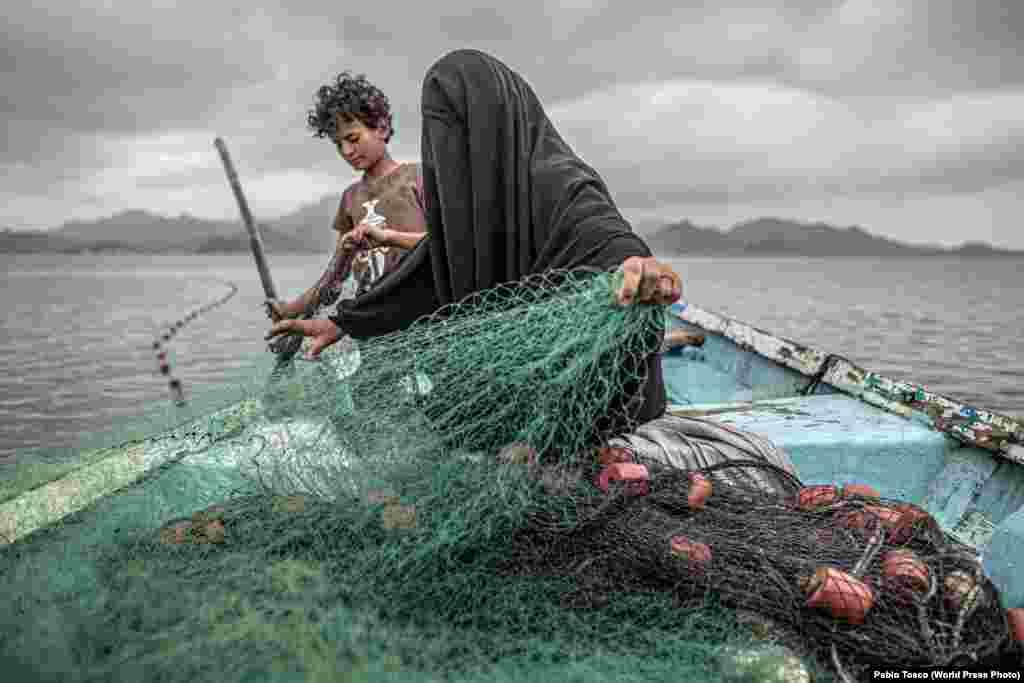 Фатима с сыном готовят рыболовную сеть, Йемен (12 февраля 2020). У Фатимы девять детей, на жизнь она зарабатывает рыболовством. Несмотря на то, что ее деревня была разрушена войной, она вернулась, чтоб начать новую жизнь.Конфликт междуповстанцами-хуситами (шиитами)и коалицией арабов-суннитов во главе с Саудовской Аравией начался в 2014 году ипривел, по мнению ЮНИСЕФ, к «крупнейшему гуманитарному кризису в мире». Первое место в категории «Проблемы современности», автор – Пабло Тоско