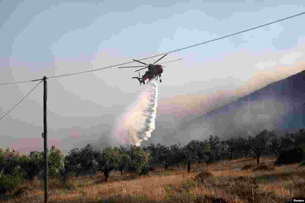 Një helikopter shihet duke tentuar të shuajë zjarret në ishullin Lesbos.