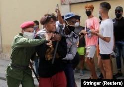 Полицейские задерживают одного из манифестантов. Гавана, 11 июля 2021 года