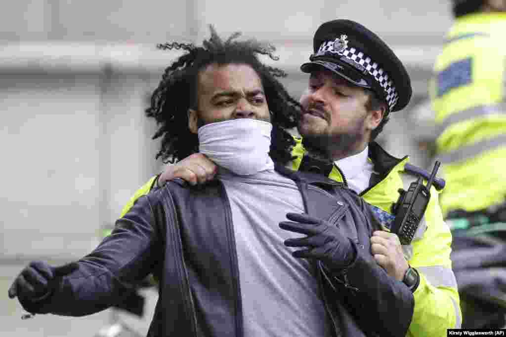 Un ofițer de poliție împiedică un protestatar să se lupte cu un trecător agresiv, în timpul unei manifestații, în Piața Parlamentului din Londra, marți, 9 iunie 2020. Adunarea a avut loc în memoria lui George Floyd.