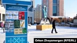 Прохожие возле агитационных плакатов. Нур-Султан, 30 декабря 2020 года.