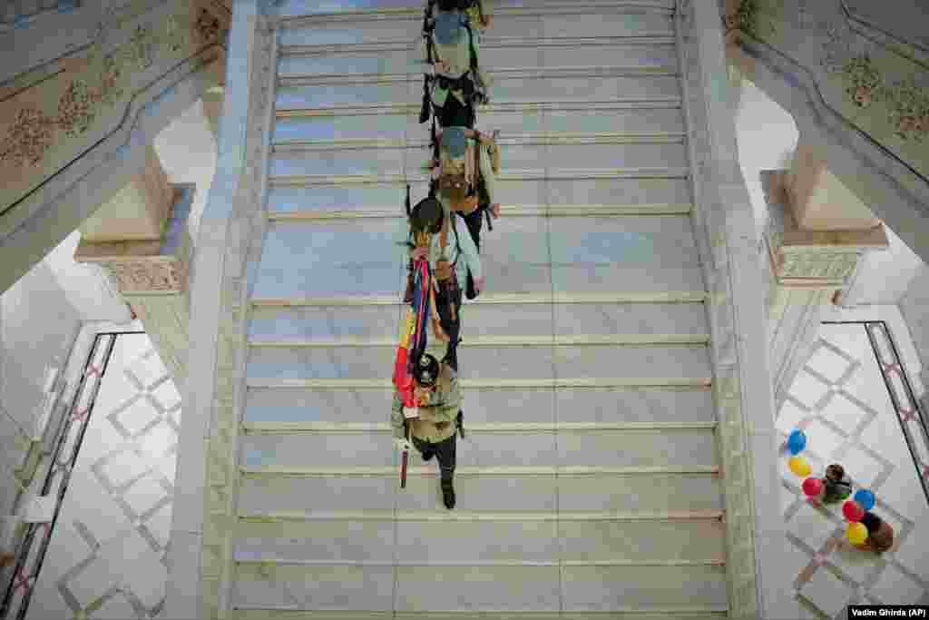 Мужчины в старинной военной форме идут по лестнице Дворца Парламента (Дома Народа) – второго по величине административного здания в мире после Пентагона, Бухарест, Румыния