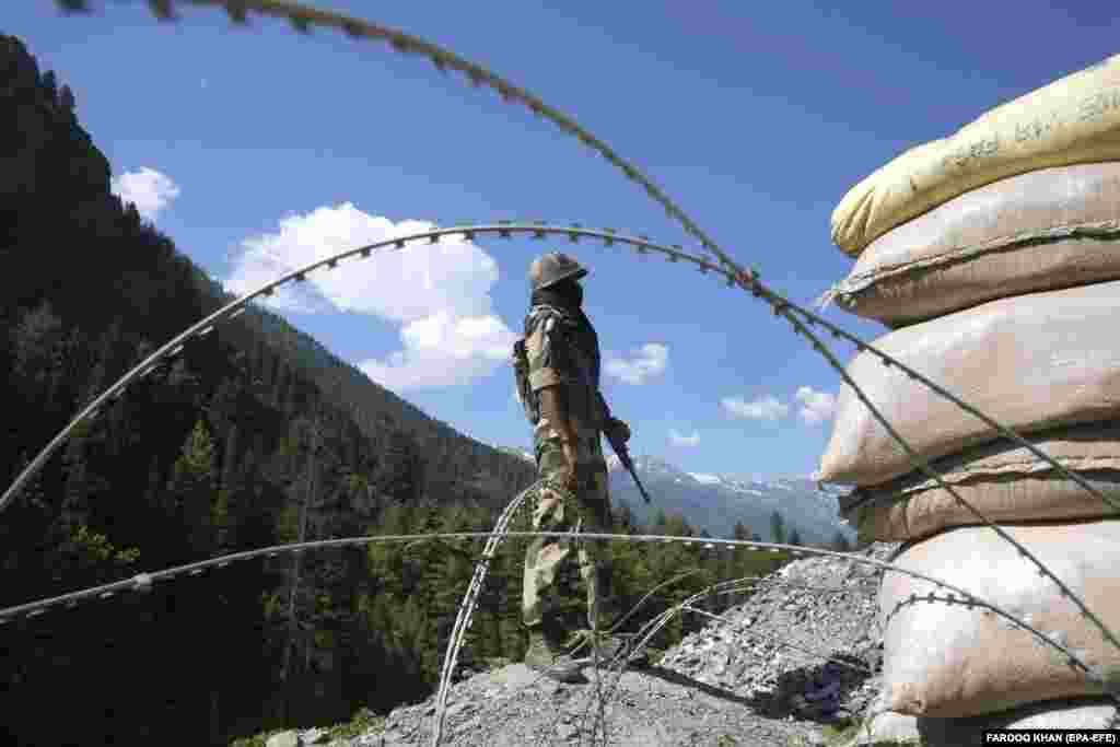 An Indian paramilitary soldier stands guard at check post along a highway leading to Ladakh, at Gagangeer some 81 kilometers from Srinagar, the summer capital of Indian Kashmir, 17 June 2020. According to news reports, twenty Indian Army personnel including a colonel were killed in the clash with Chinese troops in Galwan Valley of the eastern Ladakh region over the border fight. Military experts say one reason for the current face-off is that India has been building roads and airfields to improve transport links and narrow the gap with China's superior infrastructure on its side of the Line of Actual Control (LAC), the de facto border.
