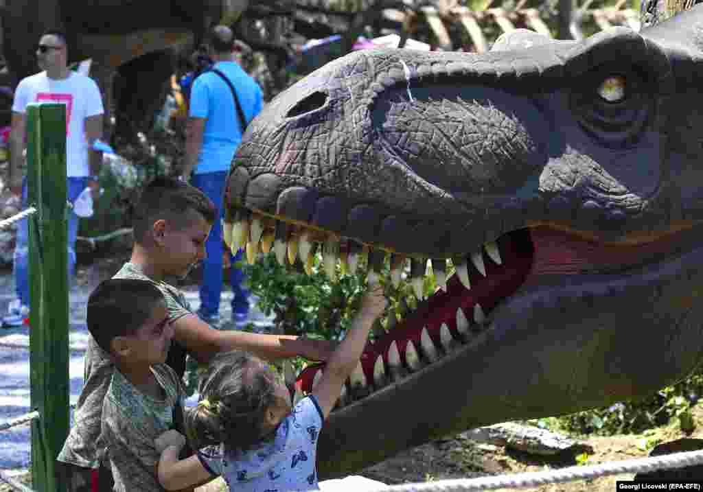 Fëmijët luajnë me një replikë të dinozaurit që është vendosur në Dino Park, një kopsht zoologjik që është hapur së fundmi në Shkup të Maqedonisë së Veriut.