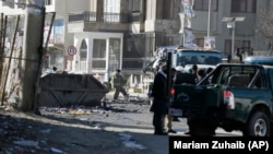 Afghan firefighters clean up the debris after a car bomb explosion in Kabul on December 31.