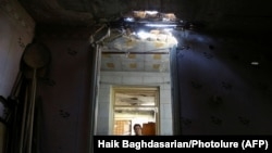 ARMENIA -- A woman stays inside a house, which locals said was damaged during a recent shelling by Azerbaijani forces, in armed clashes on the border between Azerbaijan and Armenia, in the village of Aygepar, Tavush Province, July 15, 2020