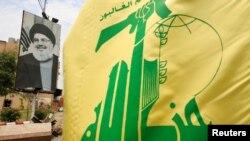 Zastava Hezbolaha i plakat koji prikazuje libanskog lidera Hezbolaha Sayyeda Hassana Nasrallaha duž ulice u blizini Sidona