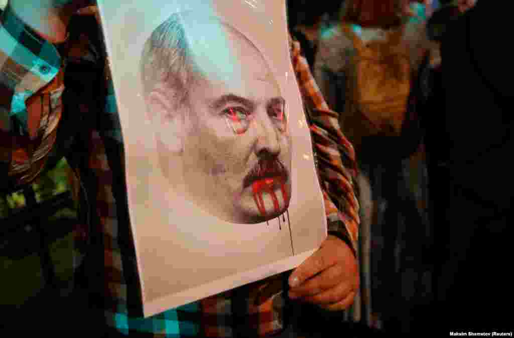 A demonstrator holds a portrait of Belarusian President Alyaksandr Lukashenka during a protest against the presidential election results outside the Belarusian Embassy in Moscow on August 11. (Reuters/Maksim Shemetov)
