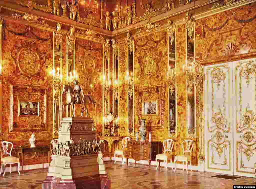 """Руската Кехлибарена стая, заснета през 1917 г. Ослепителното пространство е облицовано с тонове фино гравиран кехлибар, злато и бижута. Тя е подарена на руския цар Петър Велики от пруския крал Фридрих Вилхелм I през 1716 г. Заради своето изящество е наричана """"осмото чудо на света""""."""