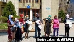 Группа граждан с портретами родственников, оставшихся в Китае и не сумевших покинуть его, перед зданием департамента консульской службы МИД Казахстана. Алматы, 14 апреля 2021 года.