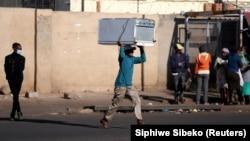 Čovjek trči nakon krađe u šoping centru tokom protesta koji su uslijedili poslije hapšenja bivšeg južnoafričkog predsjednika Jacoba Zume, Katlehong, 12. juli 2021.