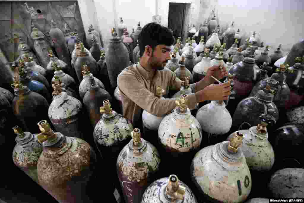 A man refills oxygen cylinders as demand for supplies rises due to a surge in COVID-19 patients in Peshawar, Pakistan. (epa-EFE/Bilawal Arbab)