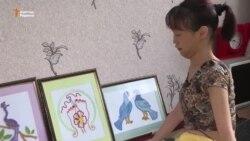 Девушка с ДЦП вышивает картины ногами