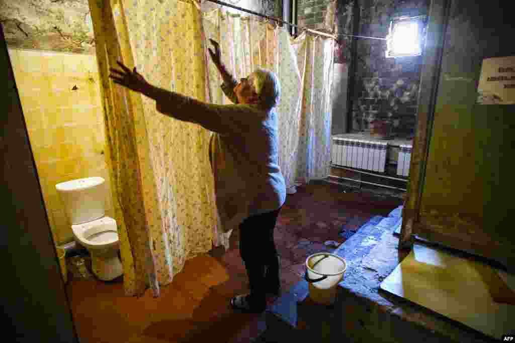 Residents share communal toilets, separated by flimsy shower curtains, and the ceilings are black with mold.