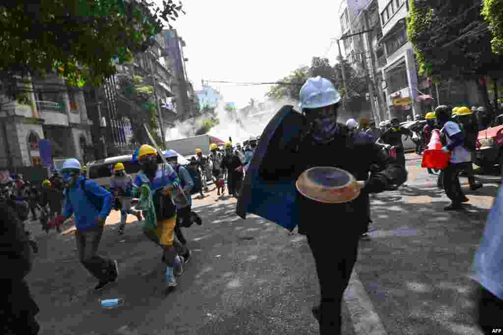 Protesters run away from tear gas from riot police during a demonstration against the military coup, in Yangon on March 2, 2021.