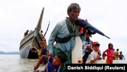 Egy rohingya férfi húzza magával a gyermekét a bangladesi part felé, miután hajóval átkeltek a Bengáli-öblön 2017. szeptember 10-én.