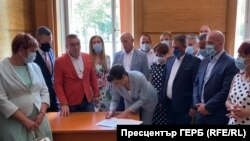Председателят на парламентарната група на ГЕРБ Даниела Дариткова подписва писмото до другите парламентарни групи пред погледа на свои колеги. Действието се развива в стаята на ГЕРБ в Народното събрание.