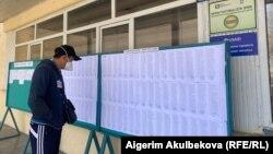 Неизвестный гражданин просматривает списки избирателей.