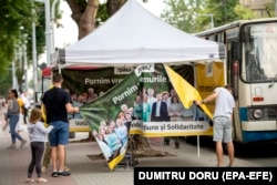 Supporters of the Party of Action and Solidarity (PAS) of President Maia Sandu at their electoral tent in Chisinau. Various scenarios include the PAS gaining an outright majority -- or falling just short and entering a coalition with Dignity and Truth.