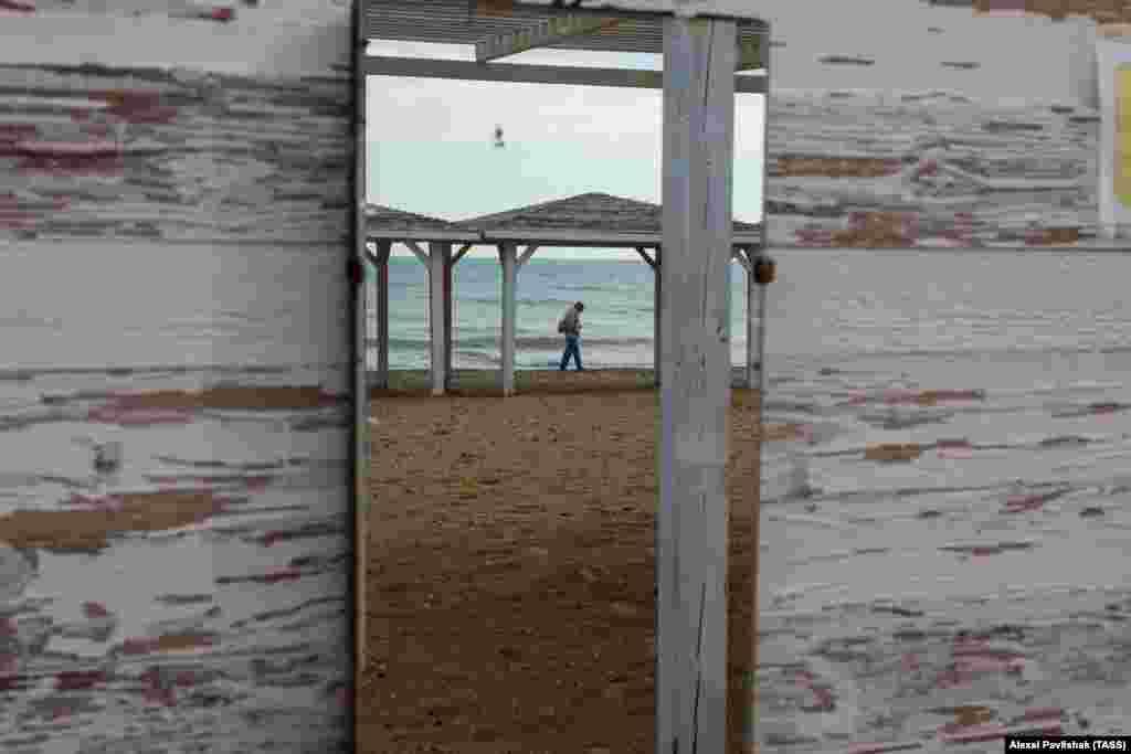 Сквозь отверстие в бунгало видны одинокие отдыхающие